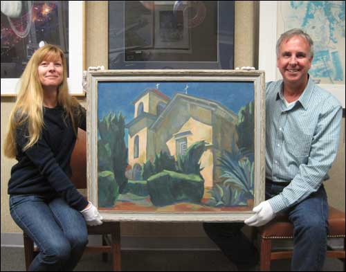 "Keith Venter and April Gage holding the Gene McComas painting ""Mission San Juan Bautista."""